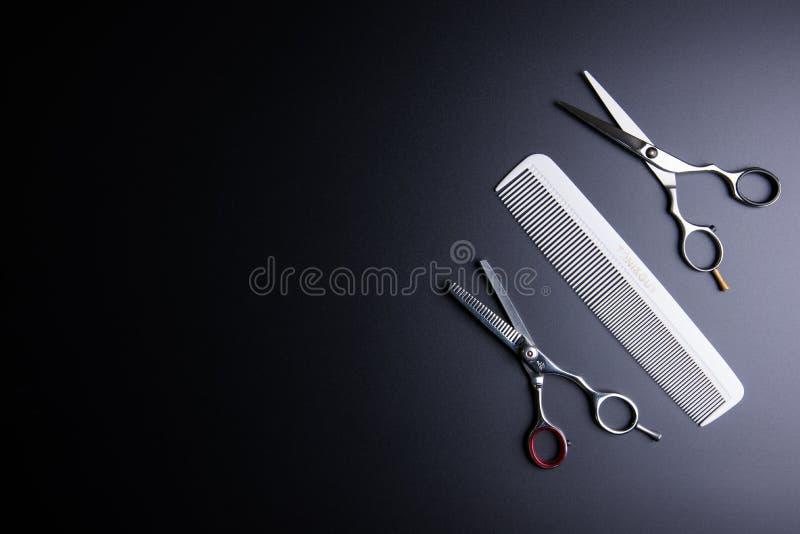 时髦的专业理发师剪刀和白色梳子在黑bac 库存图片