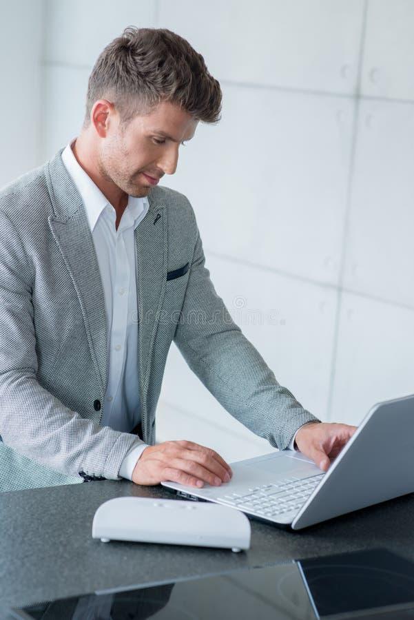 时髦的人坐的键入在膝上型计算机 免版税库存照片
