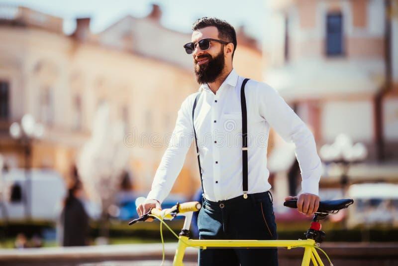 去年轻时髦的人工作在自行车旁边 有一辆fixie自行车的行家在街道上 看起来有胡子的人去,当乘坐在他的时 免版税库存图片