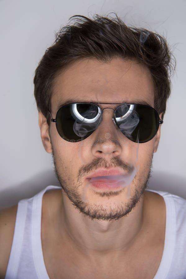 年轻时髦的人抽烟的香烟 免版税库存图片