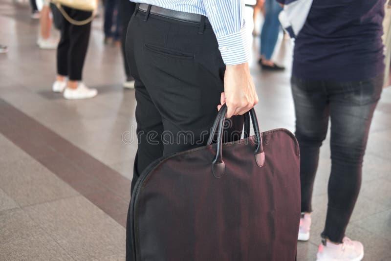 时髦的人是站立和拿着黑提包,当努力去做在公共交通工具时的工作 库存照片