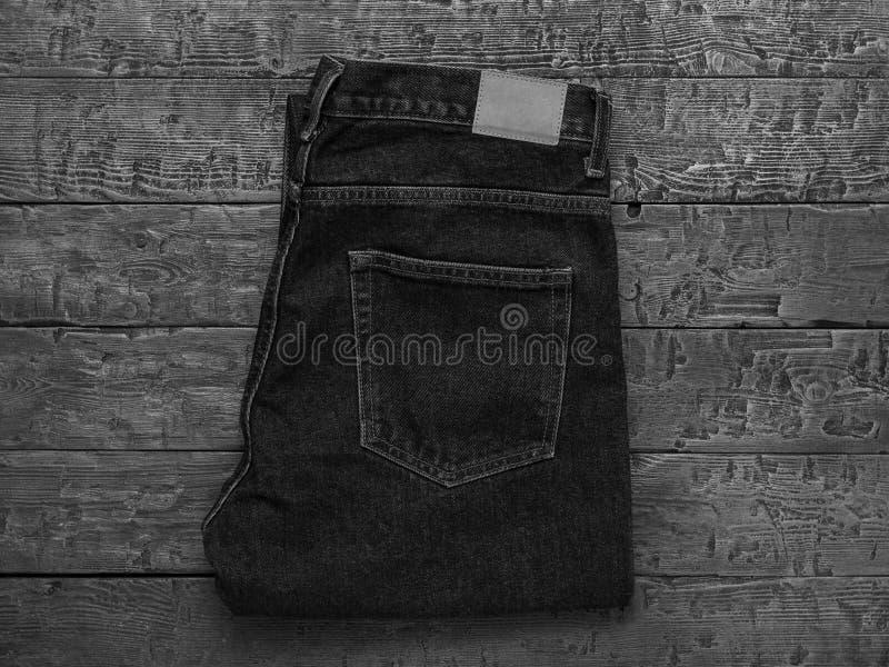 时髦的人的牛仔裤的黑白图象在一张木桌上的 经典牛仔布衣物 r 库存照片