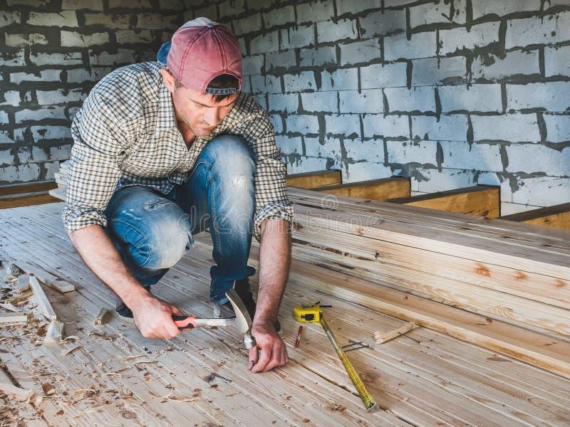 时髦的人,与在木头的工具一起使用 库存照片
