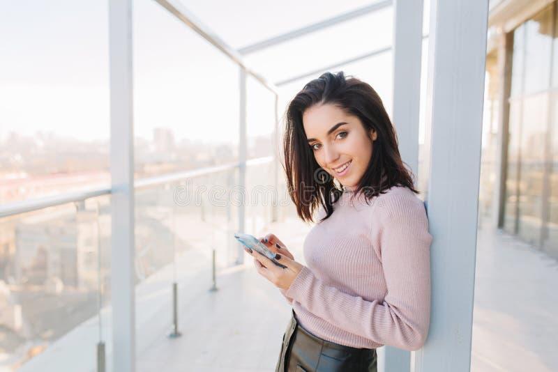 时髦的使用在大阳台的城市画象年轻时兴的深色的妇女电话在cityview背景 有吸引力 库存照片