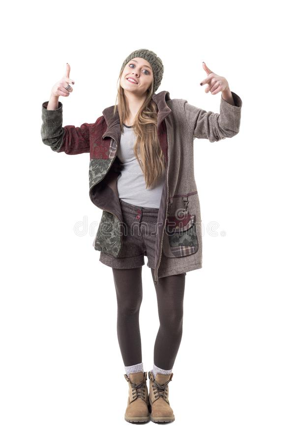 时髦的冬季衣服的凉快的质朴的反叛女孩把手指指向的照相机 免版税库存图片