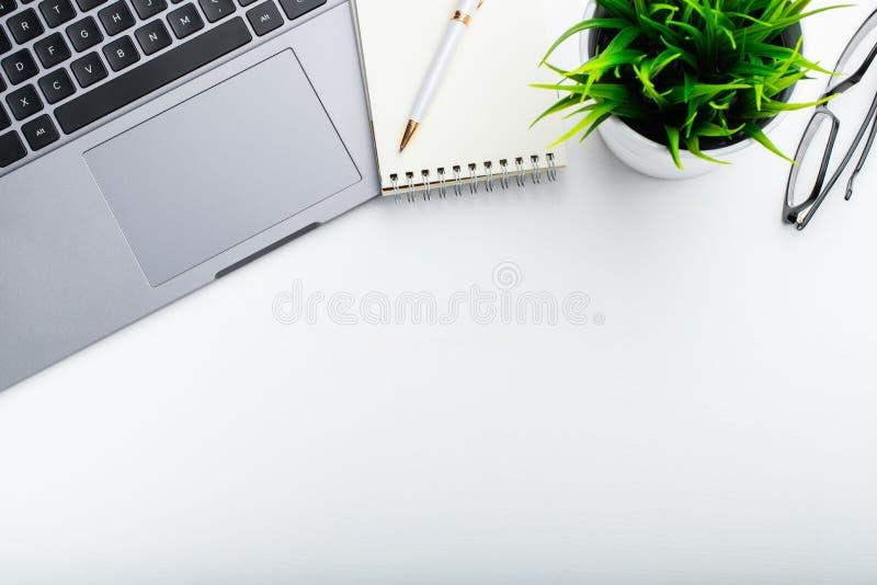 时髦的办公室桌书桌 与膝上型计算机,日志的工作区,多汁在白色背景 平的位置,与拷贝空间的顶视图tex的 免版税库存照片