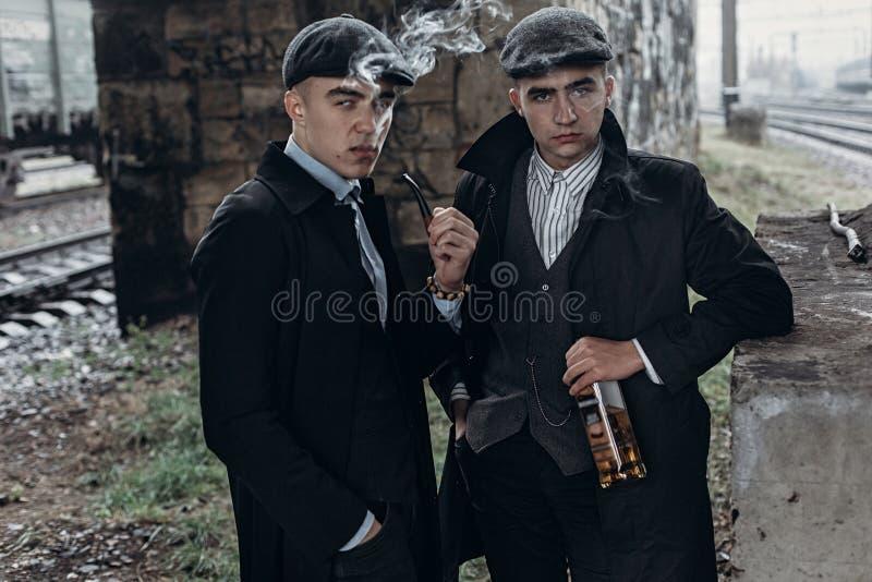 时髦的匪徒人,抽烟 摆在铁路背景  免版税库存照片