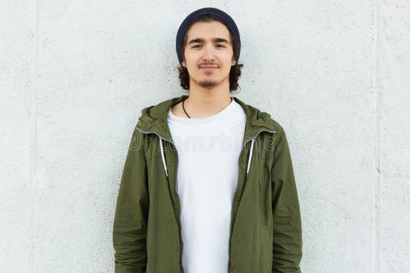 时髦的十几岁的男孩水平的射击穿黑帽会议、白色T恤杉和绿色滑雪衫,与满意的表示direclty a的神色 免版税图库摄影