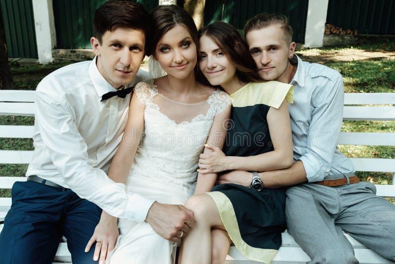时髦的华美的愉快的新娘和新郎有与朋友的照片在结婚宴会 免版税库存图片