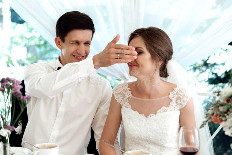 时髦的华美的愉快的新娘和新郎获得乐趣在结婚宴会,情感快乐的片刻 免版税库存照片