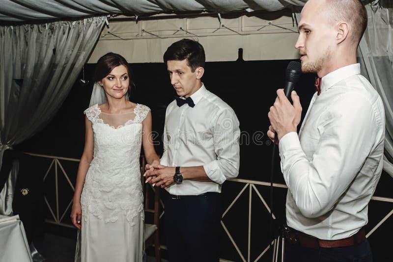 时髦的华美的新娘和典雅的新郎有宴会主持人的结婚宴会的 图库摄影