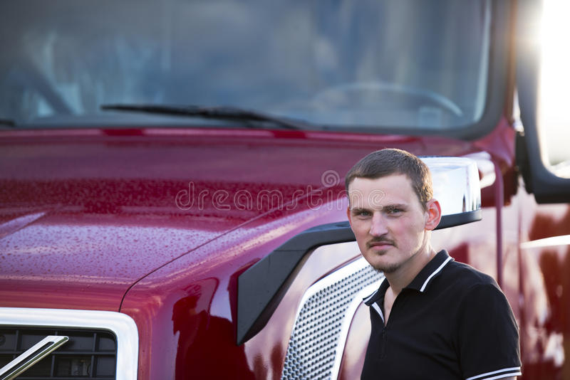 时髦的卡车司机和现代深红半卡车 库存照片