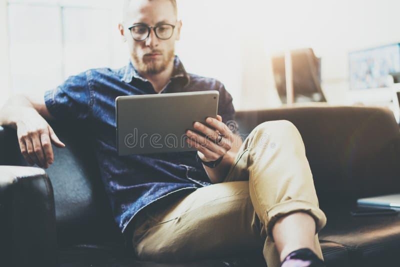 时髦的商人运作的片剂个人计算机现代室内设计顶楼办公室 人放松葡萄酒沙发用途当代设备 免版税图库摄影
