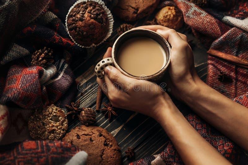 时髦的土气冬天图片用举行温暖的咖啡咕咕声的手 免版税库存照片