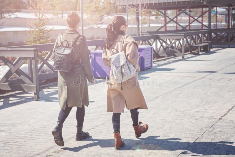 时髦的外套和背包的两个年轻朋友在城市广场走在喀山 库存照片