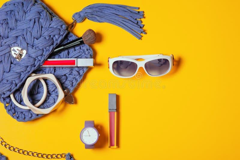 ?????????? 时髦的太阳镜、蓝色时髦被编织的手工制造袋子、紫罗兰色手表、唇膏、镯子和刷子 图库摄影
