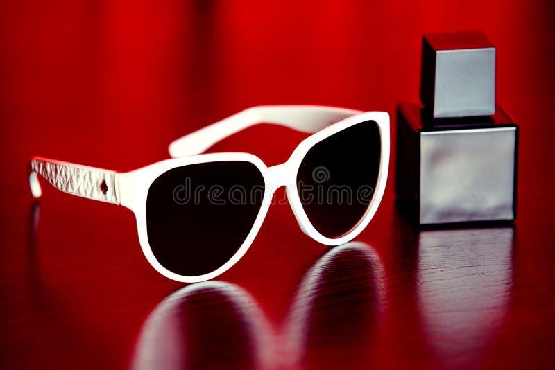 时髦的太阳镜和香水 免版税库存图片