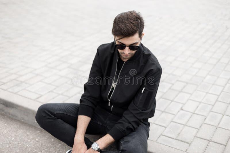 时髦的太阳镜的可爱的年轻行家人在牛仔裤的黑时兴的夹克休息在一个瓦片的开会在街道上 免版税库存照片