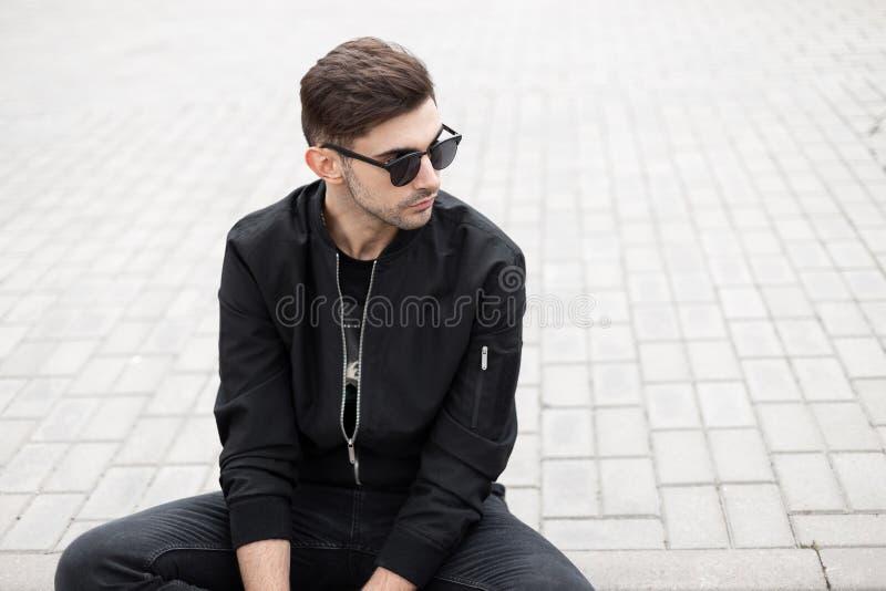 时髦的太阳镜的现代凉快的年轻行家人在牛仔裤的黑时兴的夹克在城市休息在一个瓦片的开会 免版税库存照片