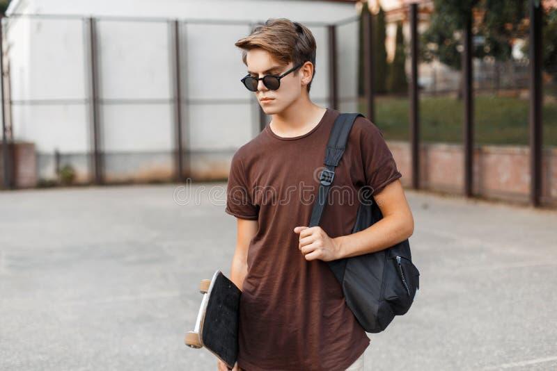 时髦的太阳镜的美国年轻行家人在有一个运动的黑背包的一件夏天T恤杉有滑板立场的 免版税库存照片