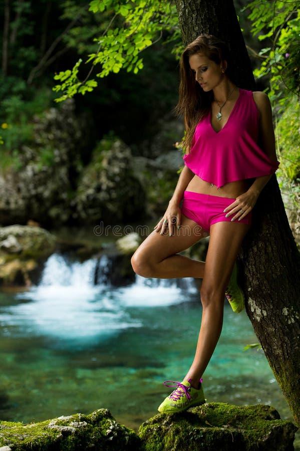 时髦的女人在河附近的黑暗的森林里 免版税库存照片