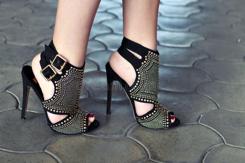 时髦的女人高跟鞋和红色钉子 免版税库存图片