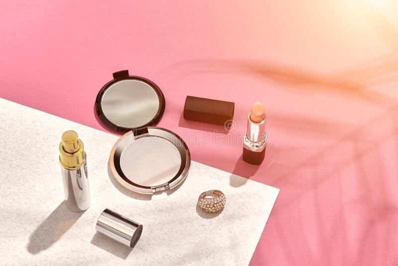 时髦的女人` s化妆用品和辅助部件 平的位置 背景桃红色白色 从棕榈叶的阴影 太阳火光 免版税库存图片