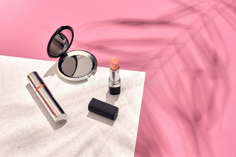时髦的女人` s化妆用品和辅助部件 平的位置 背景桃红色白色 从棕榈叶的阴影 图库摄影