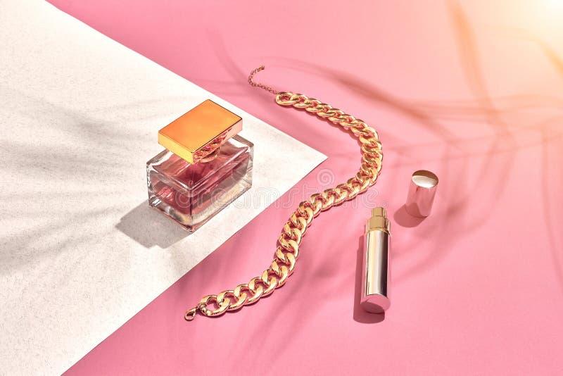 时髦的女人` s化妆用品和辅助部件 平的位置 香水 背景桃红色白色 从棕榈叶的阴影 图库摄影