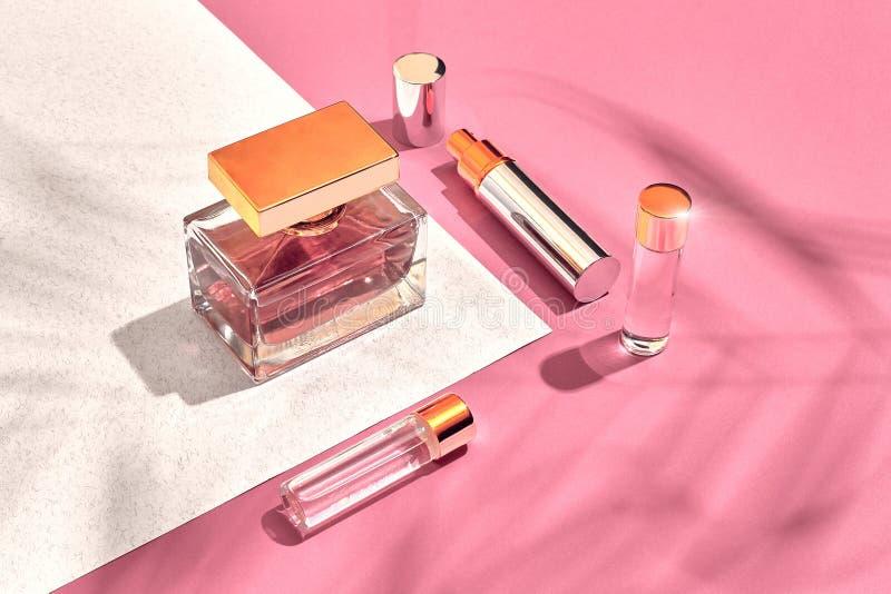 时髦的女人` s化妆用品和辅助部件 平的位置 香水 背景桃红色白色 从棕榈叶的阴影 免版税库存图片