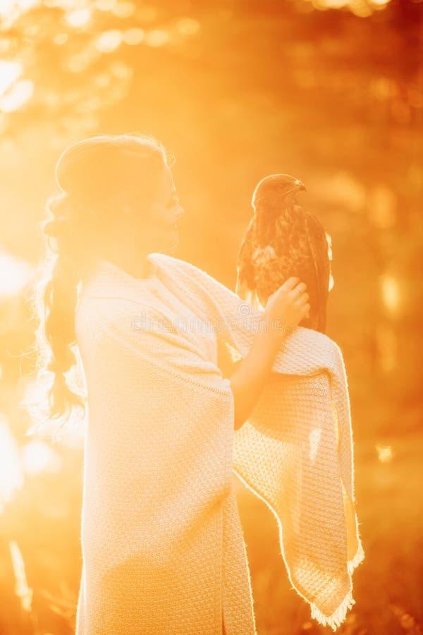 时髦的女孩和一只猎鹰在落日的光芒的秋天森林里 免版税库存照片