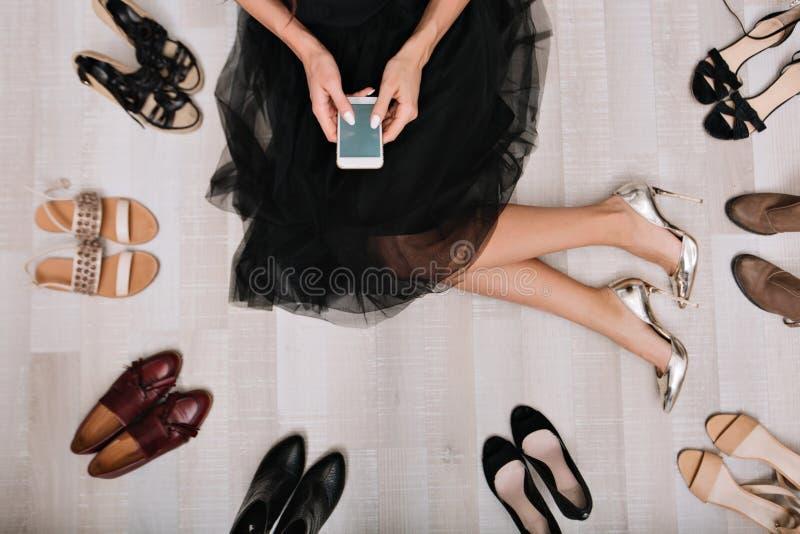 时髦的女孩坐地板在有智能手机的一间化装室在手上,写消息,围拢由a 免版税库存图片