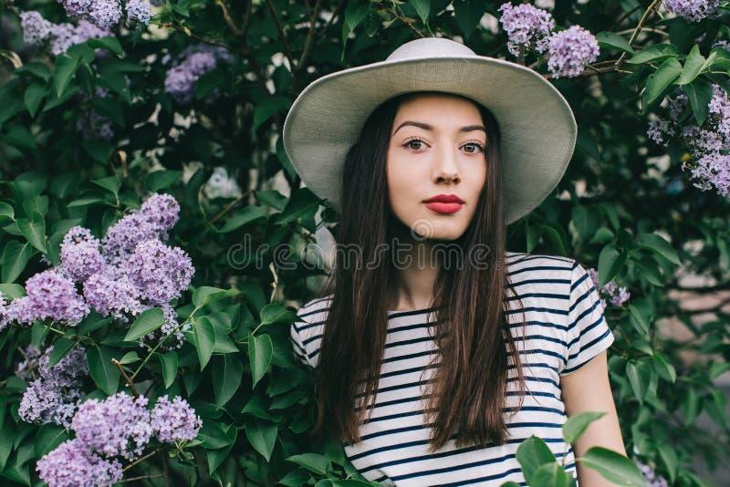 时髦的女孩行家画象在街道上的在开花的丁香中 库存照片