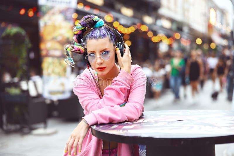 时髦的女孩,戴着时髦的眼镜,戴着头戴耳机,听前卫风格的音乐,酷的时髦的女孩,喜欢看 免版税库存图片