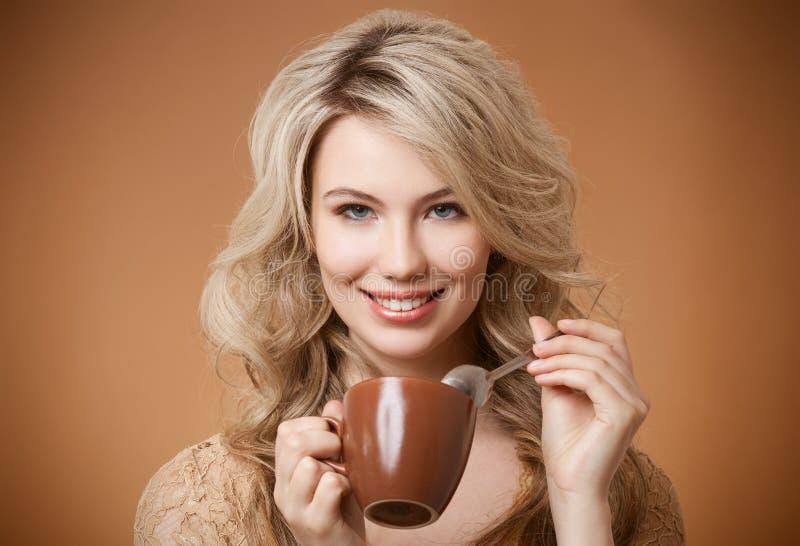 时髦的妇女用咖啡在手上 库存照片