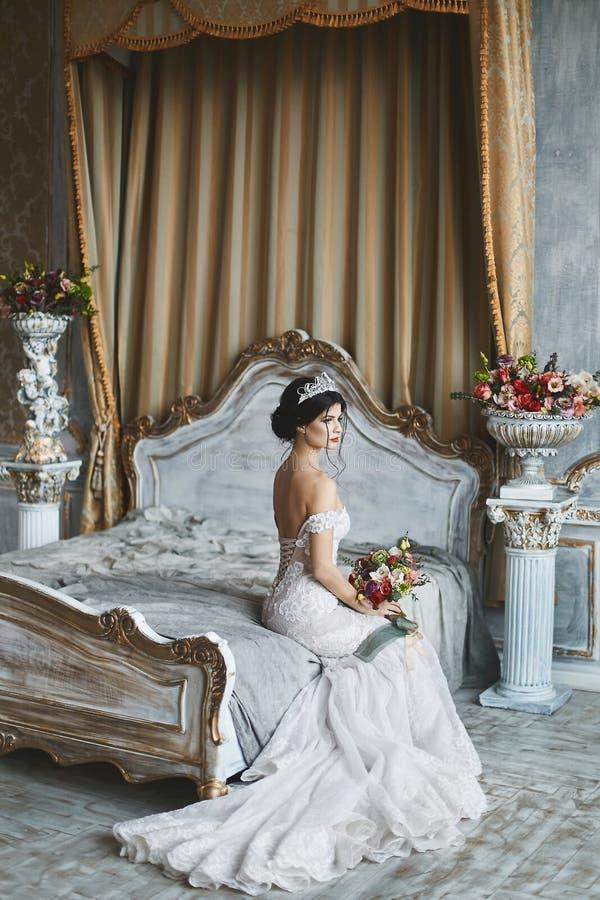 时髦的婚礼礼服的美丽和时兴的深色的式样女孩与赤裸肩膀坐与花束的床 免版税库存照片