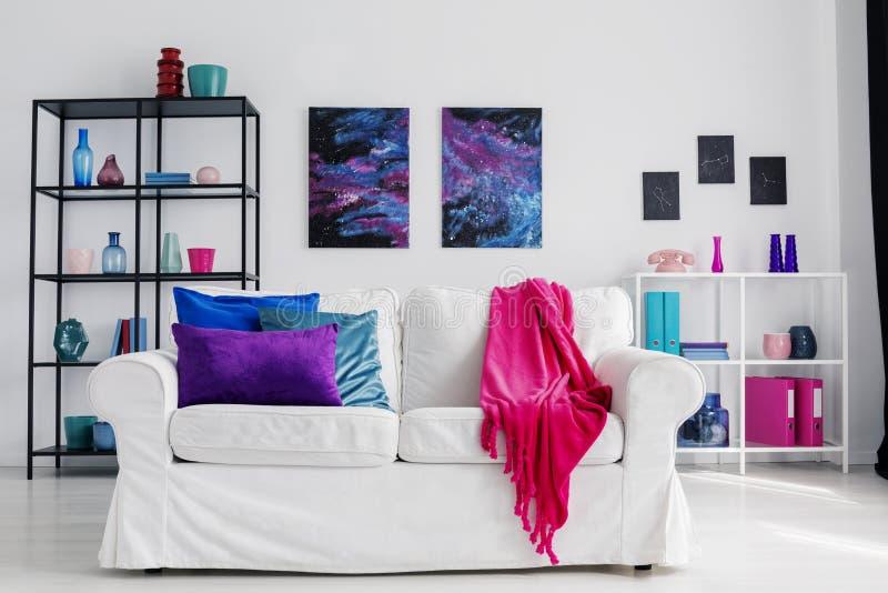 时髦的客厅垂直的看法有舒适的白色长沙发的有桃红色毯子和蓝色和紫色枕头的,波斯菊图表o 免版税库存照片