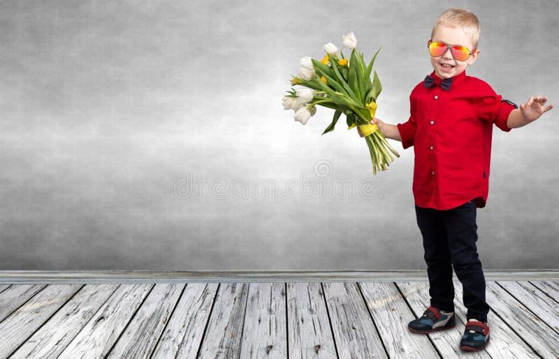 时髦的小男孩拿着春天郁金香花束  春天,假日,儿童的时尚 免版税图库摄影