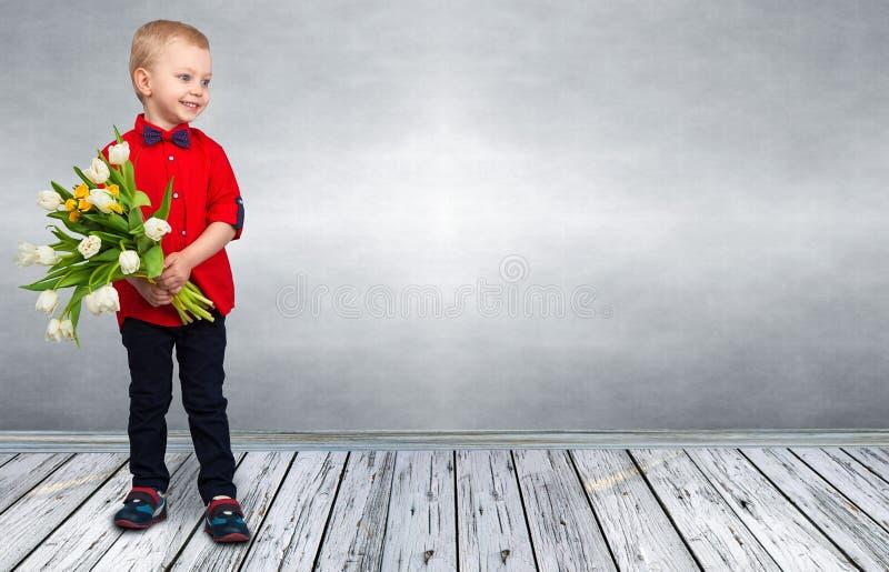 时髦的小男孩拿着春天郁金香花束  春天,假日,儿童的时尚 免版税库存照片