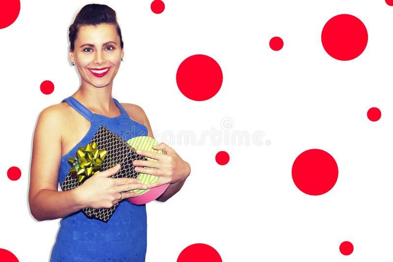 时髦的少妇画象有Xmas礼物的 微笑和在手上的时装模特儿拿着礼物盒 免版税图库摄影