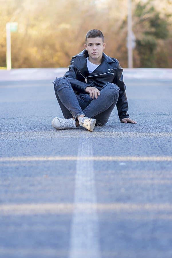 时髦的少年坐穿皮夹克的路 库存照片