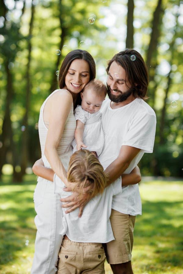 时髦的年轻家庭有休息在公园 爸爸和妈妈拿着胳膊的女儿并且拥抱儿子 免版税库存图片