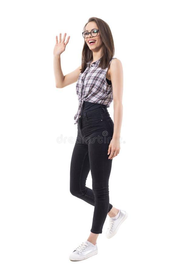 时髦的年轻激动的愉快的深色的秀丽步行,波浪手和招呼看的某人  免版税库存图片
