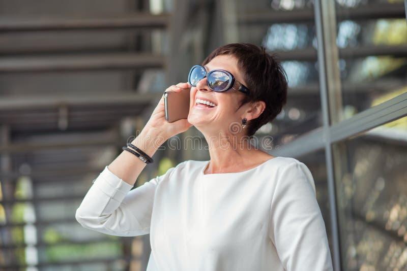 时髦的年迈的妇女说在街道上的电话里 免版税库存照片
