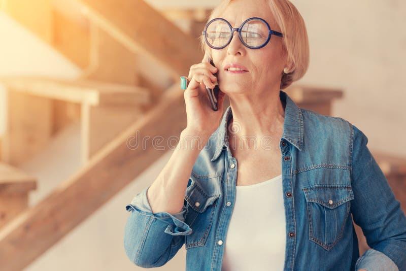 时髦的年长妇女谈话在电话 免版税图库摄影
