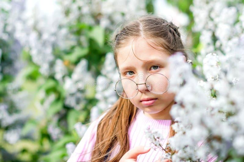 时髦的微笑的青少年的女孩画象戴眼镜的在街道 免版税库存图片