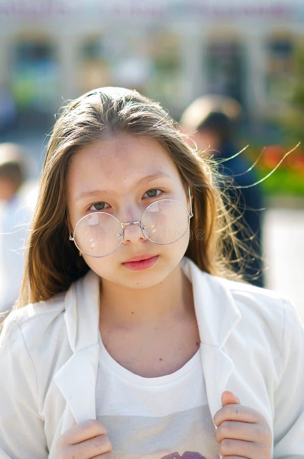 时髦的微笑的青少年的女孩画象戴眼镜的在街道 库存照片