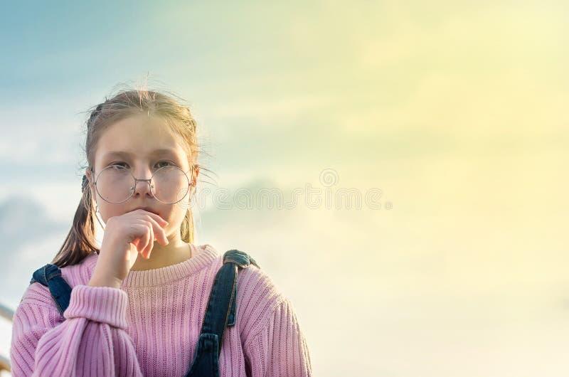 时髦的微笑的青少年的女孩画象戴眼镜的在街道 库存图片
