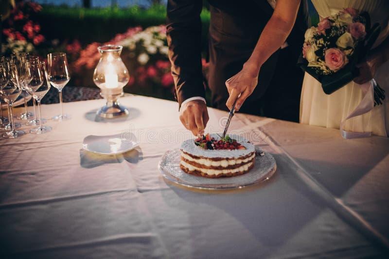 时髦的愉快的切一起婚宴喜饼用果子的新娘和新郎在结婚宴会户外在晚上 结合手 免版税库存照片