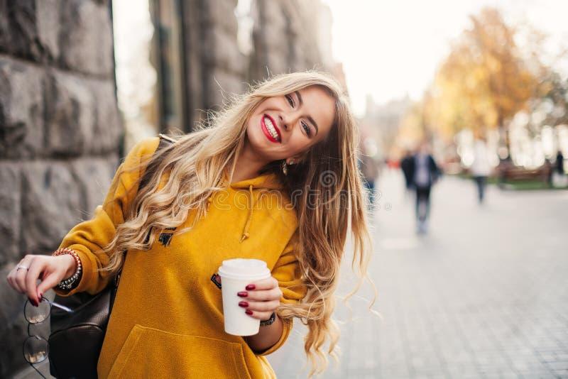 时髦的愉快的少妇佩带的boyfrend牛仔裤,白色运动鞋明亮的黄色sweetshot 她拿着咖啡去 smili画象  免版税库存照片
